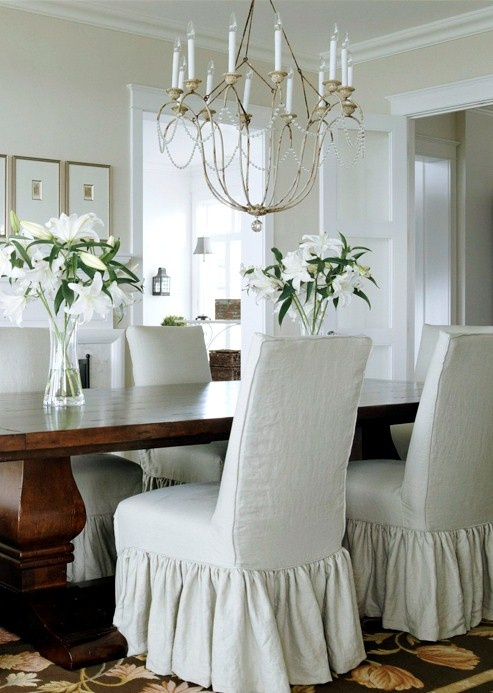 A palette inspired by nature creates a serene scheme in this vintage-look dining room. Architectural details add subtle interest to the clean design while down-to-earth furnishings, including a large trestle table and slipcovered chairs, anchor the room.    The dining chairs are dressed in easy-to-launder slipcovers.  Dark wood floors ground the space without appearing heavy.  Wide moldings, paneled doors, and dark wood floors create a vintage look.