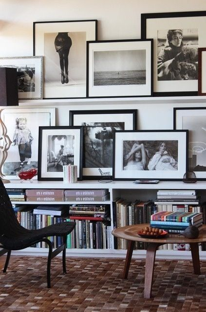 Framed black & white photographs over low bookcase.