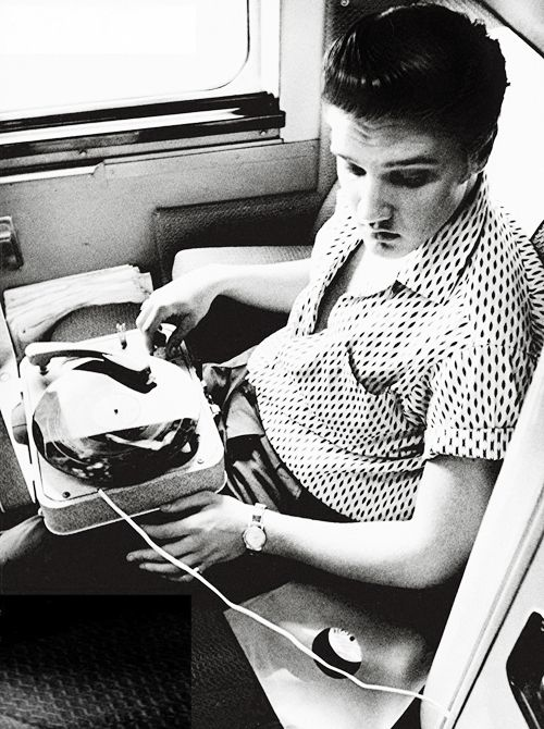 Elvis Presley listening to his portable record-player while taking the train home from New York City, 1956