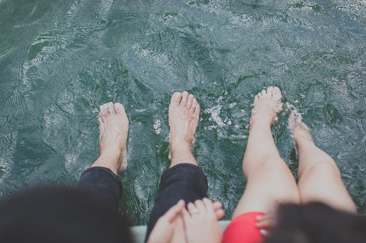 Feet in water, hand in hand. Photography by Jonah Sun, principal photographer of All Aflutter