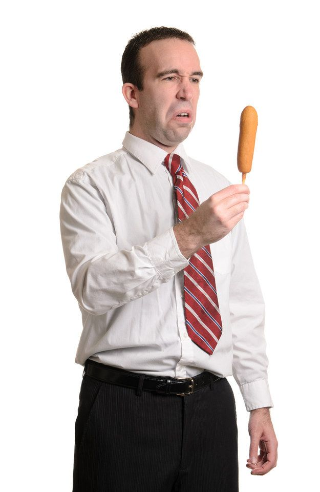 A man who doesn't quite grasp the idea behind a corndog: | 50 Completely Unexplainable Stock Photos No One Will Ever Use