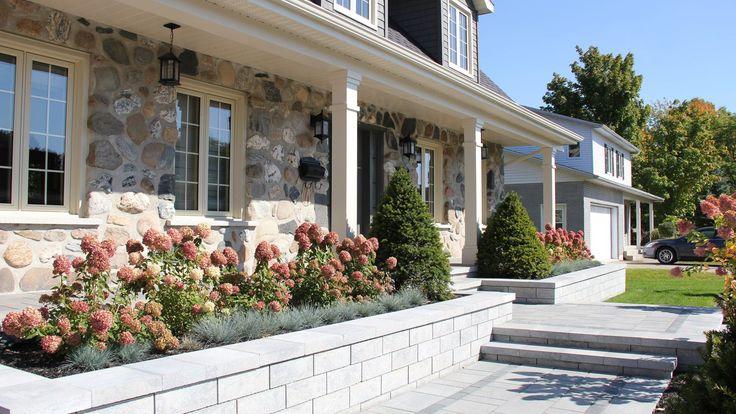 Pour cette résidence de style canadien , où les propriétaires souhaitaient actualiser et épurer leur façade, l'équipe de conception a misé sur le principe de symétrie pour valoriser l'architecture de la propriété. Afin de mettre en valeur l'accès principal à la résidence, un majestueux trottoir linéaire, bordé de plantations bien structurées a été proposé. Le
