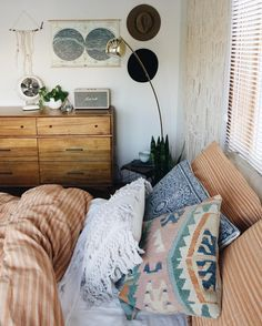 A recipe for a lovely bedroom: soft earth tone shades, and as many creative, bohemian pillows. Add golden or copper accents for a unique effect!