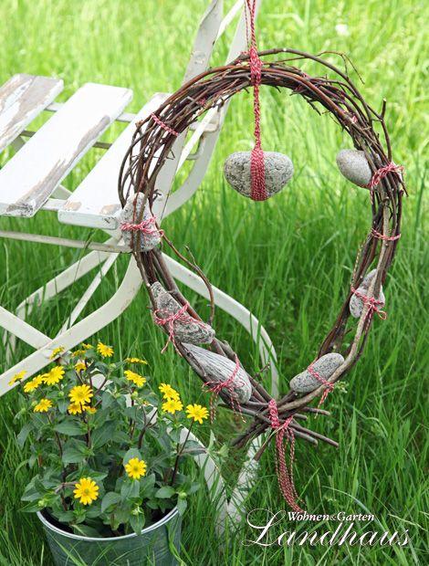"""Kranz """"Made by me""""      Junge Buchenzweige von grünen Blättern befreien und zu einem leicht ovalen Kranz binden. Untere Enden mit einer rot-weißen Kordel zusammenbinden. Verschiedene Steine mit der Kordel am Kranz befestigen. Ein Kordelstück oben am Kranz anbinden und schon kann man ihn aufhängen. (Foto: WS/Gabriele Keil)"""