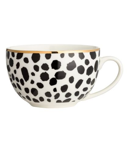 White/black. Porcelain cup with a printed leopard pattern, gold-colored rim, and printed text detail inside. Height 3 in., diameter at top 4 1/2 in.