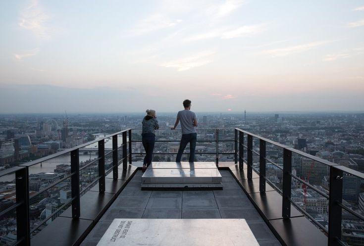 Un pareja mira asomada en la ciudad de Londres desde un piso superior de un rascacielos de nueva construcción , el edificio Leadenhall. El rascacielos , situado en la ciudad de Londres , ha sido bautizada como la ' Cheesegrater ' por su forma distintiva . El edificio se sitúa en 224 metros de altura y fue diseñado por el ' Rogers Stirk Harbour and Partners ' .