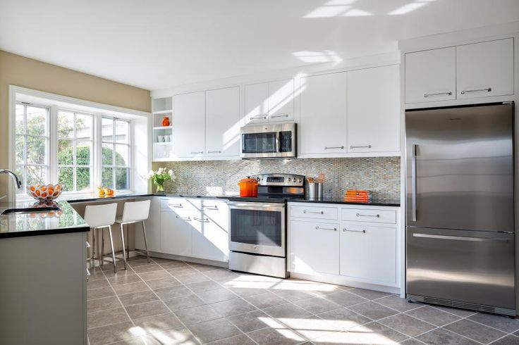 A light, bright kitchen makes the most of the basement space in this transitional home. The room features neutral walls, clean lines and white cabinetry. Wide windows take advantage of the views and bring in natural light. Quartz countertops, modern barstools and a glass tile backsplash give the room contemporary flair, and cabinetry extends to the ceiling to maximize storage.