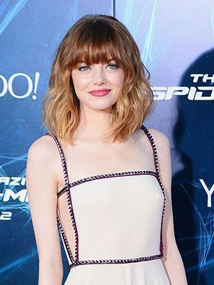 Emma Stone at the New York Spiderman Premiere with wavy hair with bangs and pink-red lipstick | allure.com
