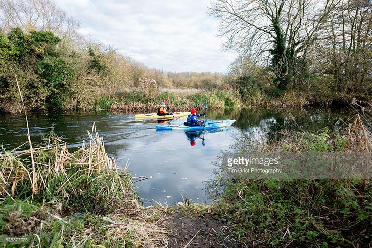 Two men canoeing on a river in the Essex countryside on a sunny winters day.