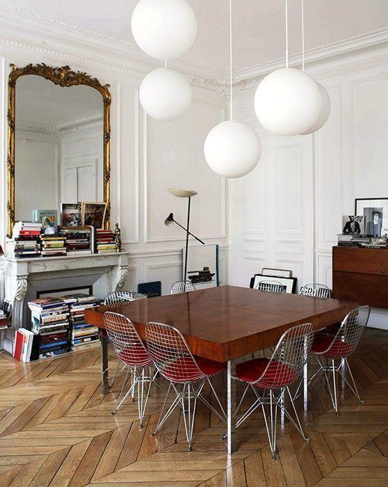 Wohn- / Esszimmer und ein Kamin voller Bücher, Spiegel, kreisrunde Lichter. Fischgrätholz