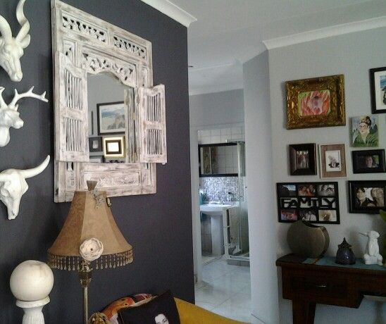 Feature walls dont have to be dreary. White on black & opposite wall of photos