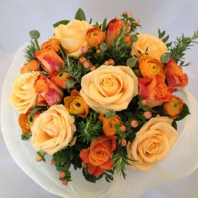A delightful bouquet of peach Roses, complemented with orange Roses, Ranunculus, foliages and berries. Presented in a wrap of Mesh.  Part of our Mothers Day 2016 Collection.