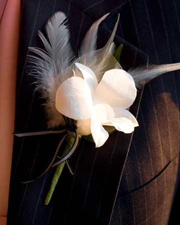 At this black and white wedding in New York City, the groom wears a small white flower accented by white feathers and a black ribbon. -- Martha Stewart Weddings