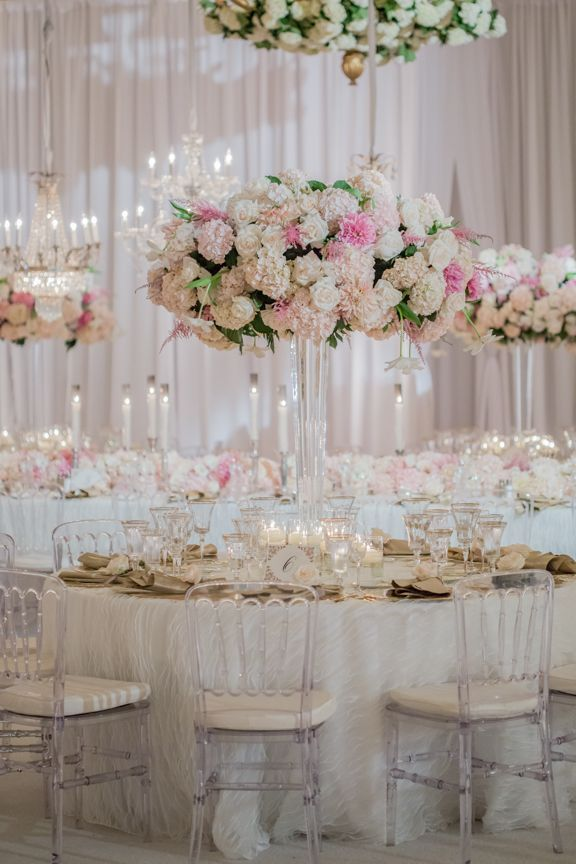 Modern clear chairs surrounded tables adorned with tall, pink and ivory flowers. #WeddingDecor Photography: Amy & Stuart Photography. Read More: http://www.insideweddings.com/weddings/chic-white-blush-gold-seaside-wedding-at-montage-laguna-beach/676/