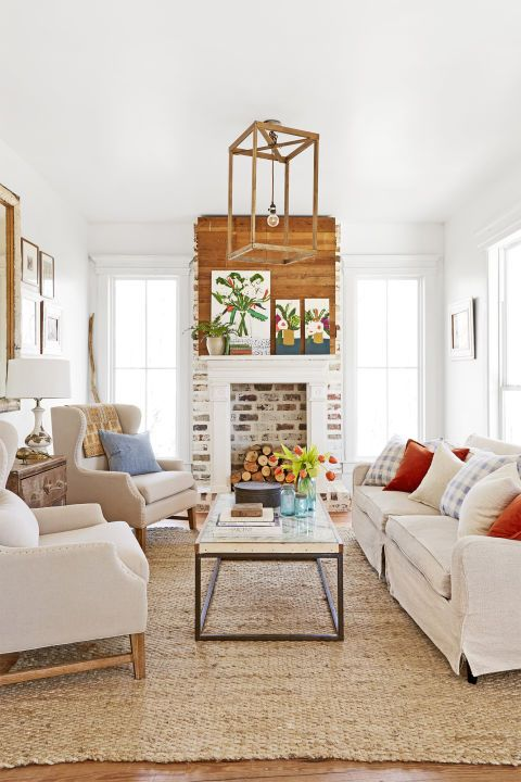 "In the family room, the couple used old paving bricks to give the fireplace a been-around-forever feel. Neutral furnishings—a slip-covered sofa (stashhome.com), a pair of armchairs (jossandmain.com), and a coffee table Tim built with wood from a dilapidated church—allow Natalie's paintings to be the stars. A tractor steering wheel provides the base of this DIY chandelier featuring wire, rope, and beads. When not in use, the television hides behind wood doors. ""I don't like for the T..."