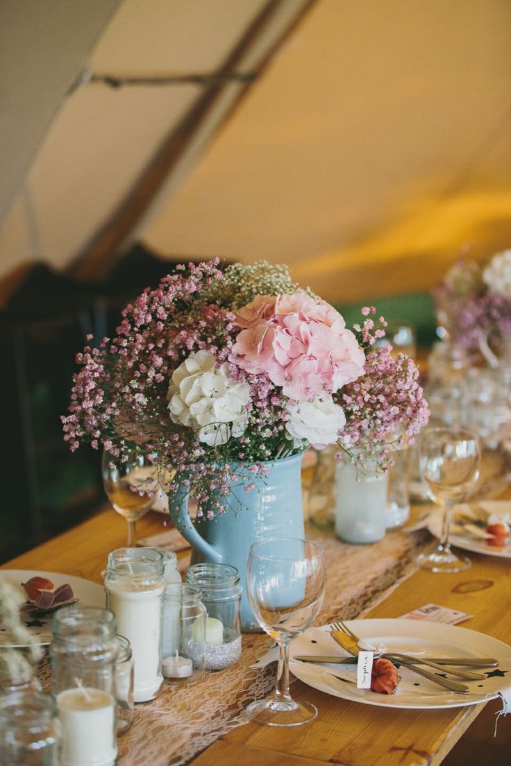 Countryside, rustic style flowers in jugs at a wedding reception. http://www.mckinley-rodgers.com/