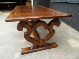 Customized solid oak dining table with shaped scrolled base