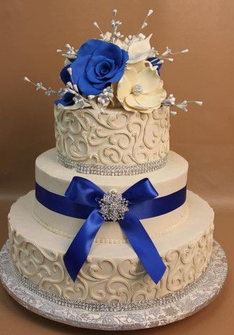 Konditor meister royal blue cake Ivory buttercream frosting with thick free form scroll on top and side with crystal banding at base. Royal blue ribbon in middle on middle tiere tied in a bow with a broach. Bouquet of rolled chocolate calla lilies, sugar magnolias, stephanotis and rolled chocolate roses in blue and ivory embellished in silver