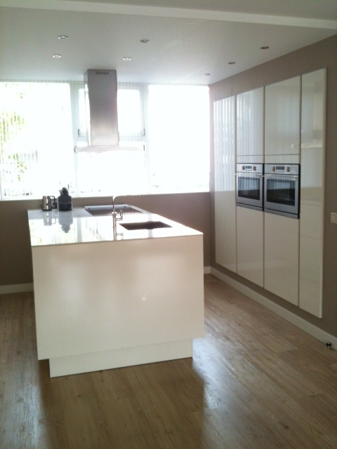 Hoogglans witte greeploze keuken met een warm licht compsiet blad. Hoge kastenwand komt met deurdikte uit de muur — in Enschede.