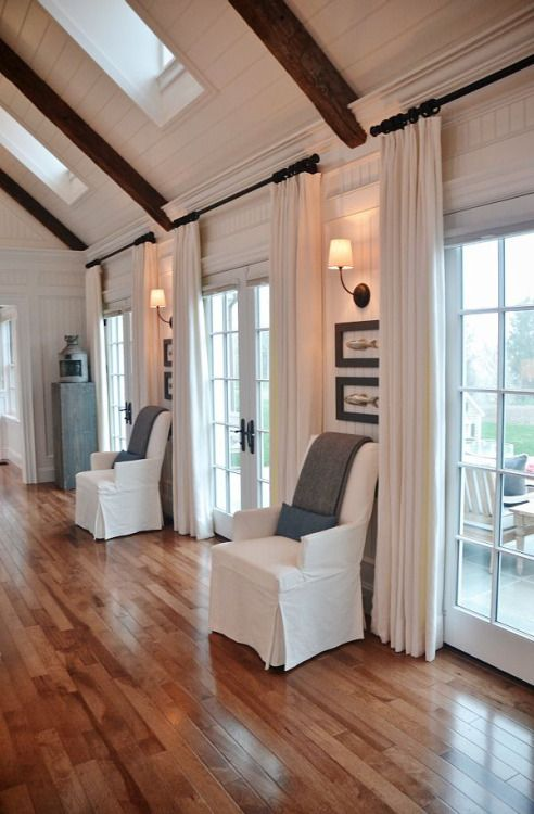Farmhouse Living Room - white planked walls, vaulted ceilings, and lots of windows.