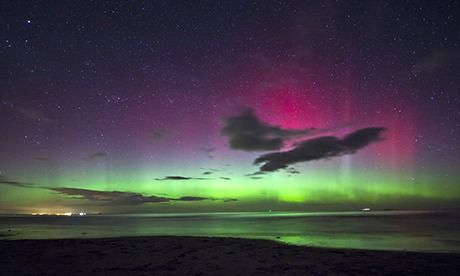 A view of the northern lights as seen from Bamburgh Castle Beach in Northumberland, England. Photograph: Josh Maidwell/Barcroft Media