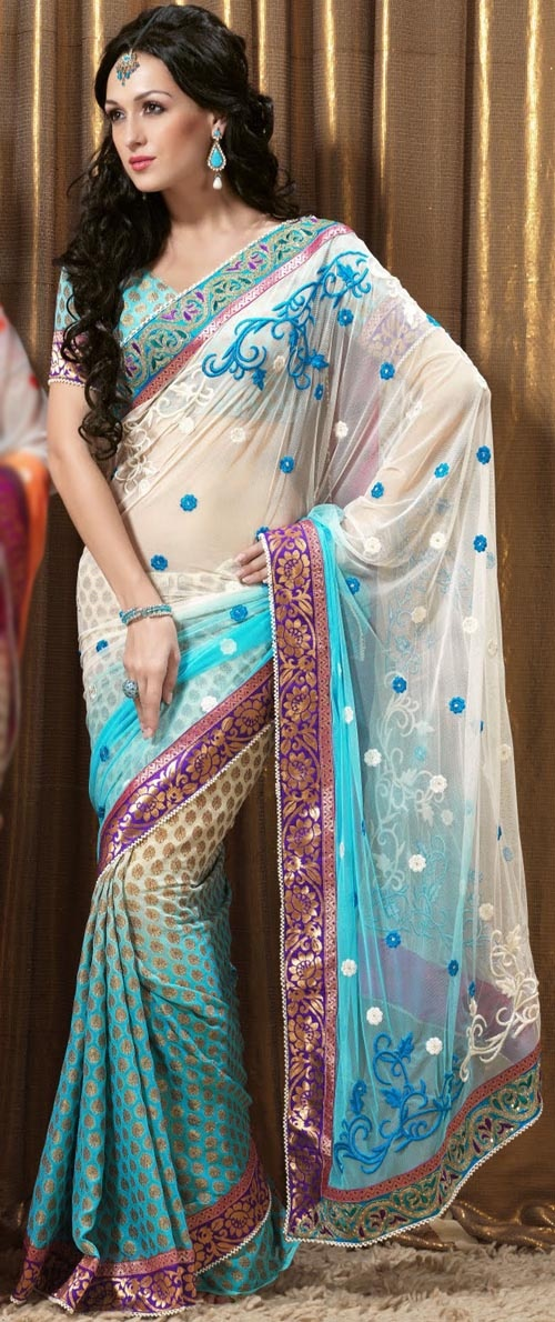 Splendid cream and blue net saree is decorated with lace, resham, stones and patch work. As shown matching blouse can be made available and also can be customized as per your style or pattern subject to fabric limitation.