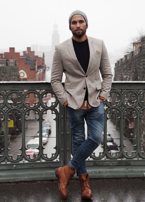 Shop this look on Lookastic:  https://lookastic.com/men/looks/blazer-crew-neck-sweater-long-sleeve-shirt-skinny-jeans-boots-beanie-watch/13092  — Grey Beanie  — Black Crew-neck Sweater  — Grey Blazer  — Dark Brown Leather Watch  — Brown Polka Dot Long Sleeve Shirt  — Navy Skinny Jeans  — Brown Leather Boots