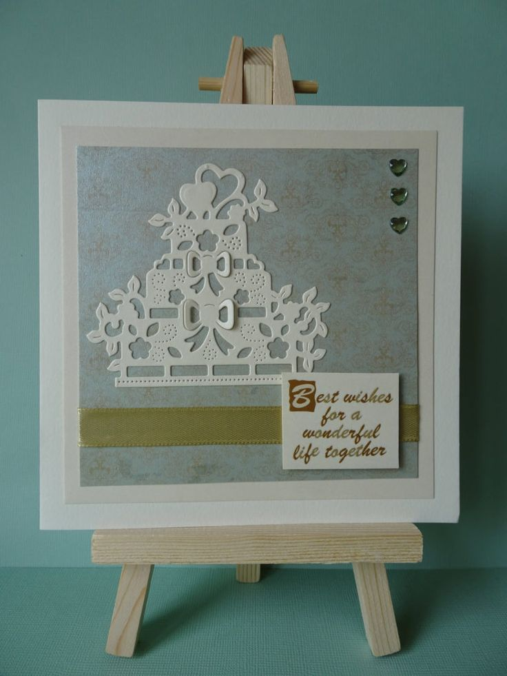 A square cream card with patterned gold and mint paper topped with a wedding…