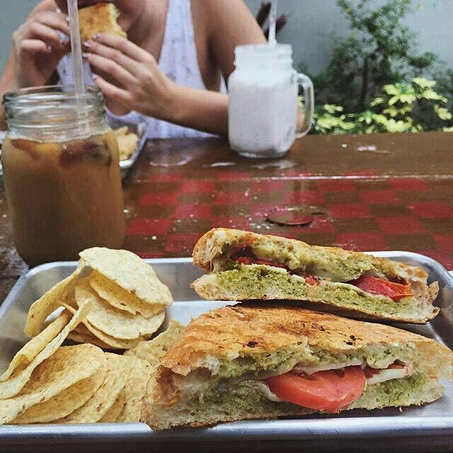 Caprazy panini, iced coffee and frappes.  Pesto, tomatoes, balsamic vinaigrette and mozzarella cheese. Beautifully hand painted chessboard on patio tables at Felicitous Coffee in Tampa, Fl