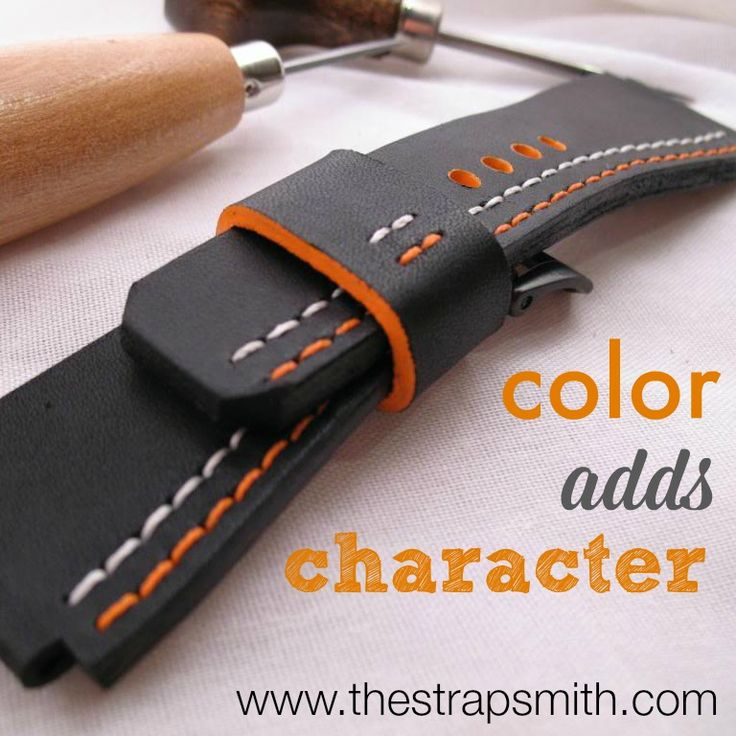 Orange and white contrast on a smooth black leather strap.