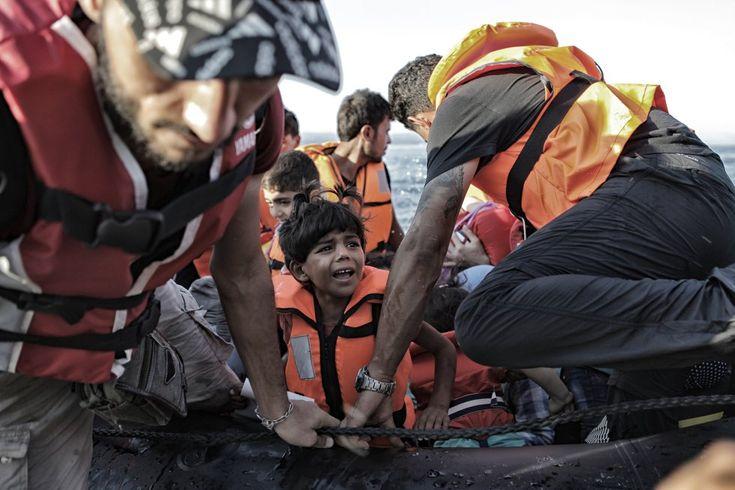 Un grupo de refugiados desciende de una barca de plástico tras cruzar el Mar Egeo desde la costa turca hasta la isla griega de Lesbos. Según EuroPol, casi 85.000 menores no acompañados (sin padres o familiares a su cargo) cruzaron el Mediterráneo para alcanzar Europa.