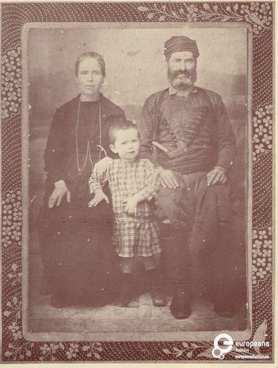 A B/W photo of a family. The man in Cretan costume.  Συλλέκτης: Peloponnesian Folklore Foundation Ίδρυμα: Europeana Fashion