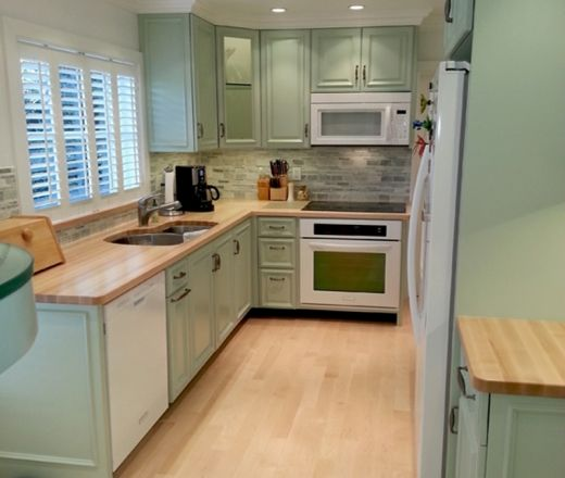 This transitional L-shaped kitchen layout features vintage green cabinets with green & white wall accents.