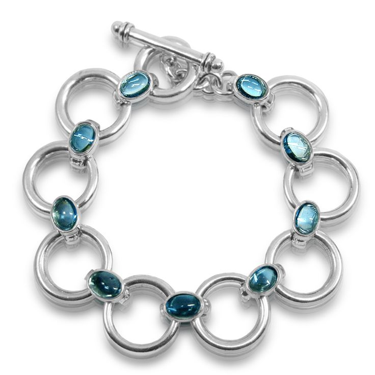"""Silver Circle Bracelet – Swiss Blue Topaz bracelet in Solid Silver  Beautiful solid silver hoops or circles with seven Swiss Blue Topaz Cabouchon links and solid silver fob. Everything we make in our Scarab workshop is SOLID silver (and solid gold – nothing is plated or hollow). You'll feel the quality in its """"weightiness"""". Our workshop craftsmen (and women) carefully select the topaz gemstones to look their best together on the bracelet."""