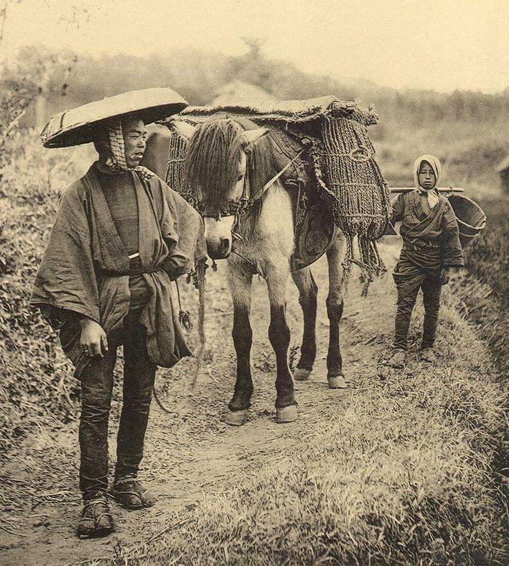 """Photograph of a Japanese man and boy, with their horse, on a country cross-road. Included in """"Japanese Life"""", ca. by Ogawa Kazumasa."""