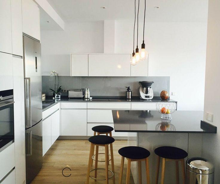 cocina integrada en el saln con encimeras negras y muebles en blanco