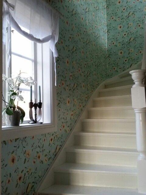 Trapphuset. Vitmålad trätrappa. Färgglad tapet från InTrade. Ljust lantligt, men inte vitt.