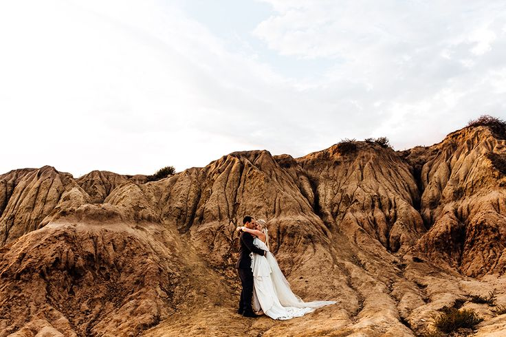San diego bohemian wedding shoot at sunset cliffs bride chiffon gown with ruffles and thin straps with low back design and plunging neckline and flower headpiece decor with groom charcoal grey suit with matching vest and white dress shirt with long teal tie hugging by rock cliffs