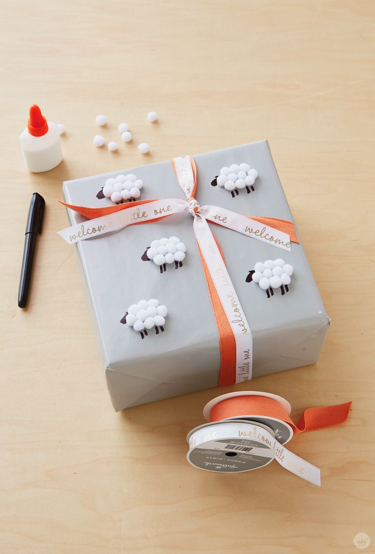 "If you're headed to a baby shower, try these gift wrap ideas to really make your gift memorable. With a little DIY magic and a sweet pattern, you can perfectly wrap a baby shower gift! Just follow this simple tutorial for this gift wrap idea: Wrap the box in gray paper and go once around with two kinds of ribbon: white grosgrain with a ""welcome little one"" message and textured orange cotton. Then glue on teeny pom-poms to make tiny sheep, and add heads and legs with a black marker."