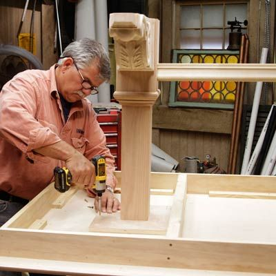 Tom Silva attaches the leg assembly to the underside of the table top for a trestle table