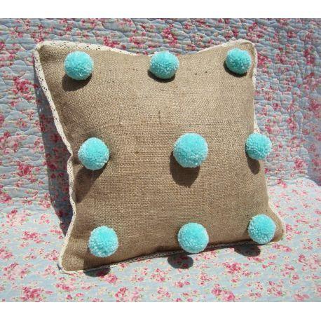 Almohadón con nueve pompones de lana sobre arpillera. Relleno vellón siliconado. Cierre que permite sacar el relleno para poder lavar. Terminación en broderie Tamaño : 40 x 40
