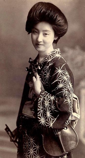 Geisha with violin 明治10年くらいからバイオリンを持つ事が流行になり、花柳界でもバイオリンを演奏できる芸者がいたそうです。 ただ、写真の女性が花柳界の方なのか、明治の演奏家なのかは、定かではありません。