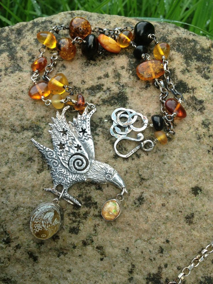 Amber silver crow pendant. Carved amber fish. Jet and amber beads. Opal. Hannah Willow Www.hannahwillow.com