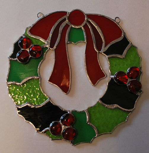This stained glass Christmas wreath suncatcher wall hanging is finished in a Tiffany style copper foil technique and is approx. 8 X 8