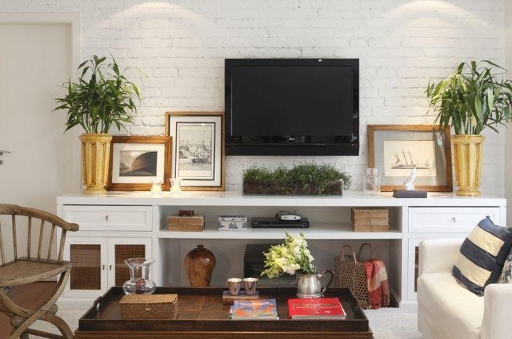 No home theater, idealizado pela In House Designers de Interiores, o estilo escolhido foi o provençal, marcado pelo relevo dos tijolos suavizado pela pintura branca. Sobre o rack, a TV é ladeada pelos quadros com molduras dourada e pelos vasos. A composição é simétrica