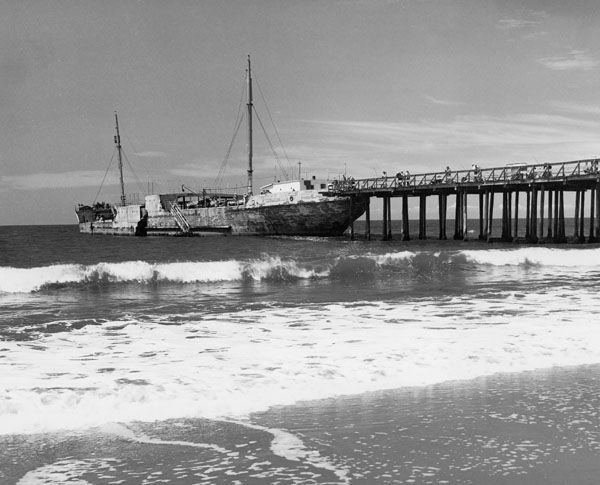 The Cement Ship, originally the Palo Alto, with fishermen on the Seacliff Pier next to it. In 1965 the ship was sold to the State of California for $1.00 and incorporated into Seacliff State Beach.
