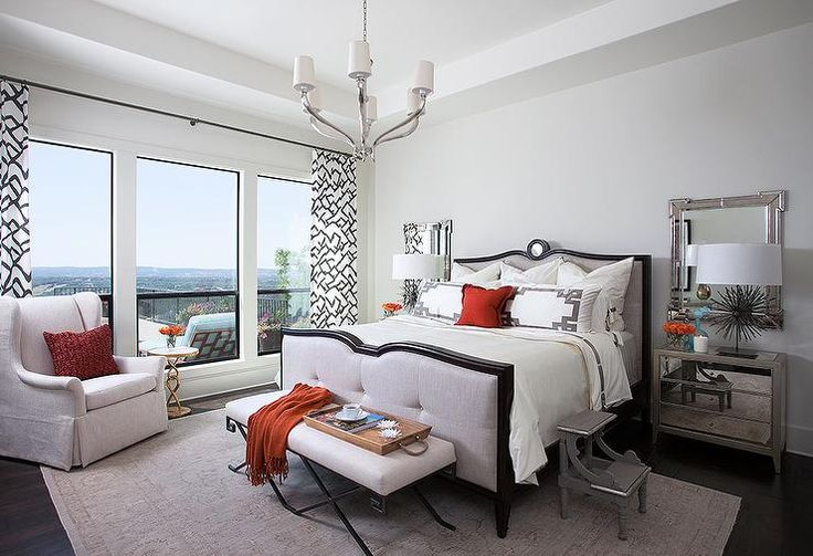 Chic bedroom features a gray tufted bed accented with dark wood trim dressed in white and gray Greek key bedding flanked by antiqued mirrored nightstands and Greek key mirrors, Mirror Image Home Key Corner Mirror.