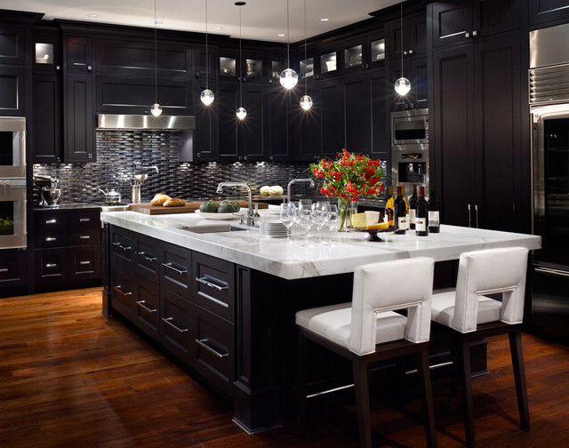 Dark cabinets, light countertop, distressed hardwood floor, teardrop island lighting
