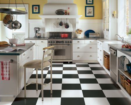This French Country kitchen gets its personality from the stylish black-and-white luxury vinyl tile flooring. The blue-and-yellow color palette, stainless steel appliances and white cabinetry bring fresh contemporary touches to this charming kitchen.
