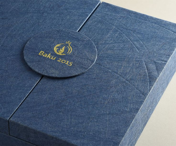#Twist #Favini - This precious paper from #Favini has been chosen to make the EOC medal boxes for the Baku Games 2015.  This unique graphic specialty, made by mixing cloth and paper, is the ideal choice for creative and luxury applications.  The blue tone selected for the medal box is decorated with gold writing. And the European Games logo has been hot embossed on the front.  The packaging is a prize in itself! Design by Eleonora Salerno www.eoodesign.com